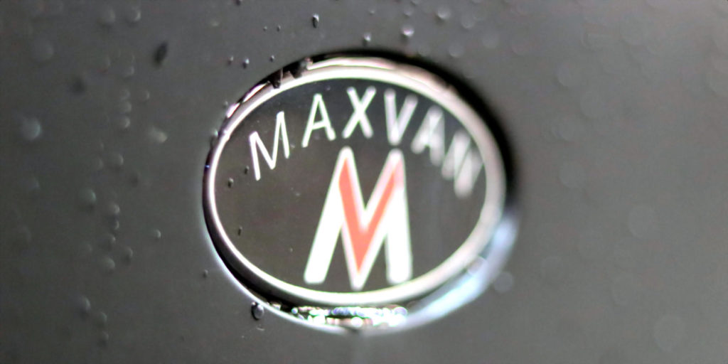 maxvan oval logo partially blurred with water drops